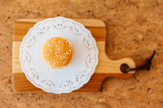 Vista superior do mini hamburguer da galinha na placa de desbastamento de madeira.