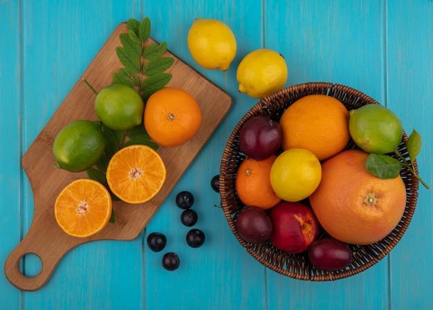 Vista superior do mix de frutas em uma cesta de toranja, laranja, limão, limão e ameixa cereja com uma tábua de corte em um fundo turquesa