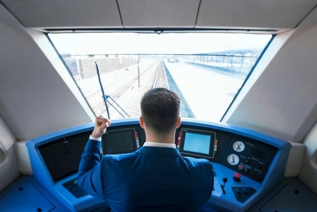 Vista superior do motorista do metrô chegando à estação a tempo com seu trem de alta velocidade