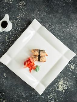Vista superior do nigiri de peixe frito servido com gengibre e wasabi