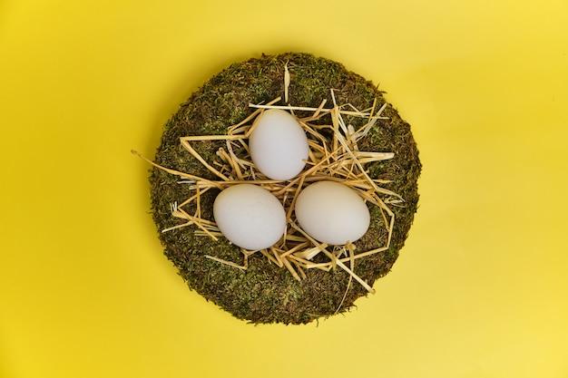 Vista superior do ninho de páscoa com ovos de páscoa em fundo amarelo