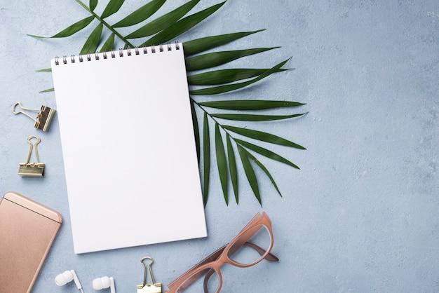 Vista superior do notebook com smartphone e folhas na mesa