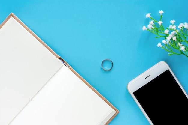 Vista superior do notebook diário aberto com smartphone e itens decorados em fundo azul