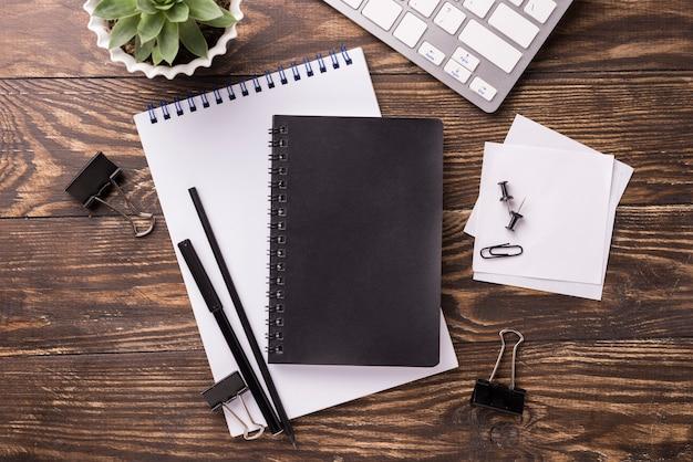 Vista superior do notebook e teclado na mesa de madeira com suculentas