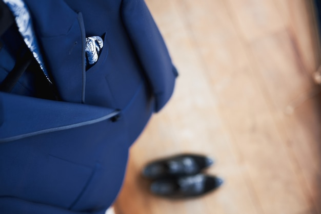 Vista superior do novo terno azul de casamento do noivo e gravata pendurado em um cabide