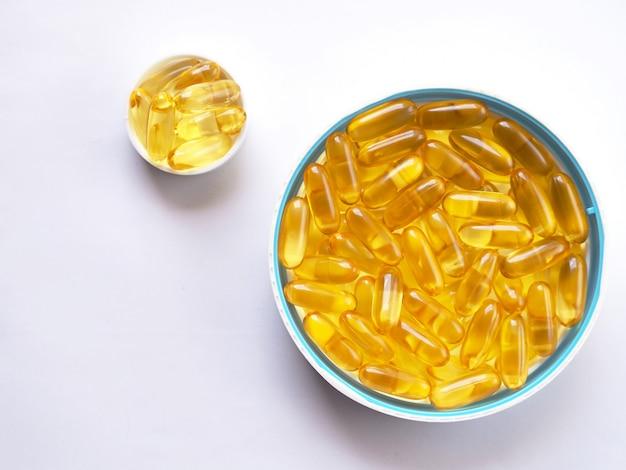Vista superior do óleo de peixes na bacia branca na tabela branca. cérebro de vitamina de óleo de peixe