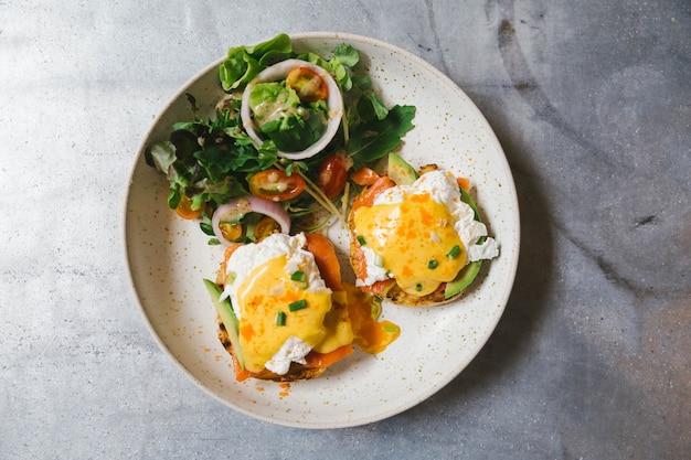 Vista superior do ovo benedict com salmões e abacate, servido com salada na placa branca.