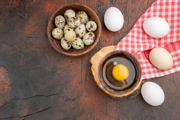 Vista superior do ovo cru quebrado dentro do prato com ovos de galinha e codorna