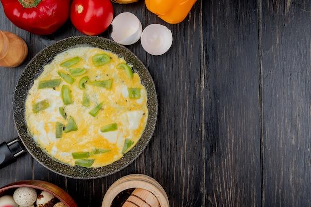 Vista superior do ovo frito com fatias de pimentão verde em uma frigideira em um fundo de madeira com espaço de cópia