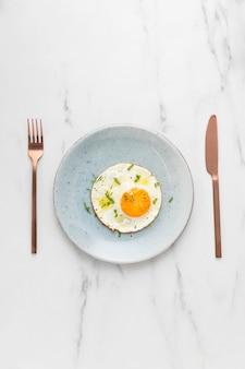 Vista superior do ovo frito com talheres no café da manhã