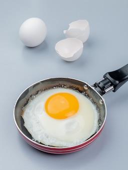 Vista superior do ovo frito em uma frigideira com casca de ovo rachada no fundo branco