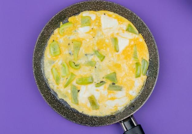 Vista superior do ovo frito em uma frigideira com fatias picadas de pimentão verde sobre fundo violeta