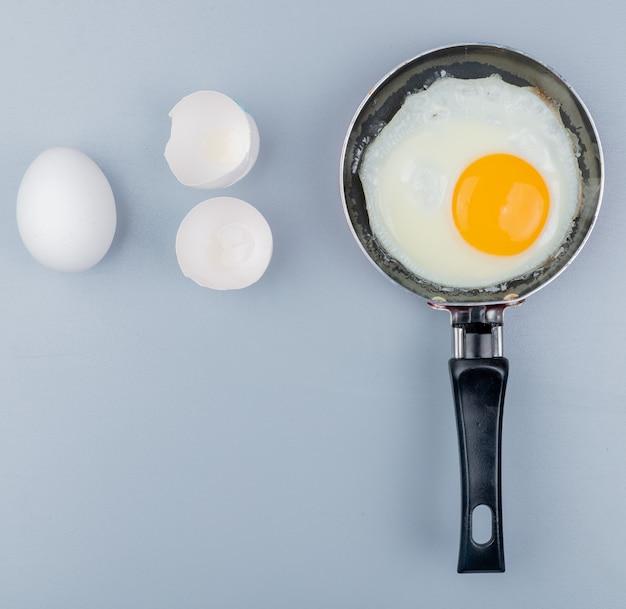 Vista superior do ovo frito em uma frigideira com ovos de galinha fresca no fundo branco