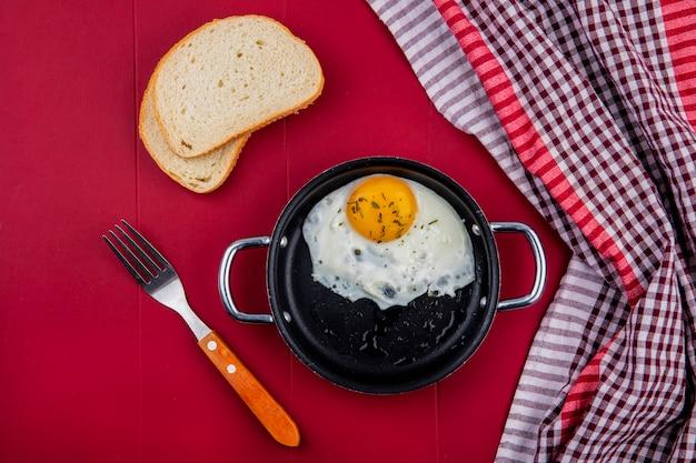 Vista superior do ovo frito na panela com fatias de pão e garfo no vermelho