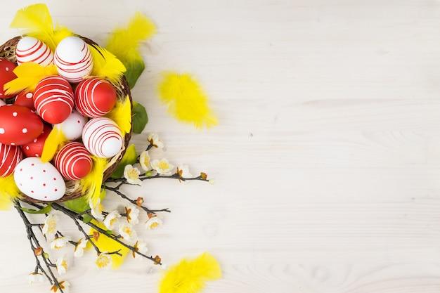 Vista superior do ovos da páscoa coloridos na cesta com penas amarelas e flores da mola em um fundo de madeira claro com espaço de mensagem.