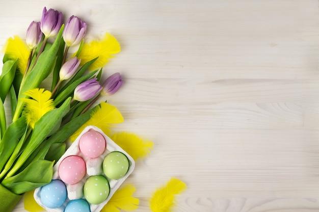 Vista superior do ovos da páscoa coloridos no cartão dos ovos com penas amarelas e tulipas roxas em um fundo de madeira claro com espaço de mensagem.