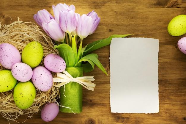 Vista superior do ovos da páscoa coloridos no ninho, tulipas roxas e cartão da mensagem no fundo de madeira marrom.