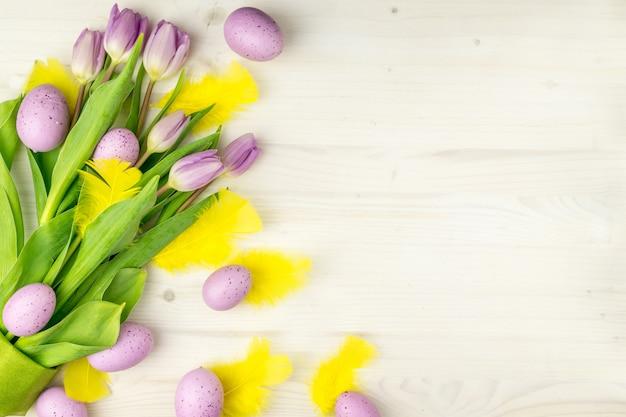 Vista superior do ovos da páscoa roxos com penas amarelas e tulipas roxas em um fundo de madeira claro com espaço de mensagem.
