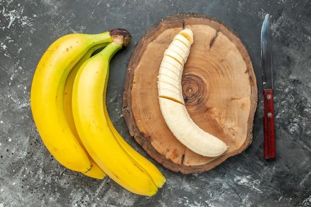 Vista superior do pacote de bananas frescas da fonte de nutrição e picado na faca da tábua de madeira em fundo cinza
