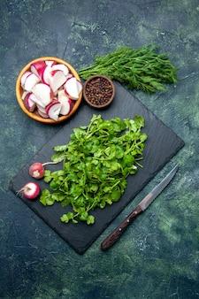 Vista superior do pacote de coentro, rabanetes inteiros frescos picados, pimenta na tábua de madeira e faca no fundo verde preto de cores misturadas com espaço livre