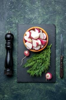 Vista superior do pacote de endro fresco e rabanetes inteiros picados em uma faca de martelo de cozinha de tábua de corte preta em fundo de cores diferentes com espaço livre