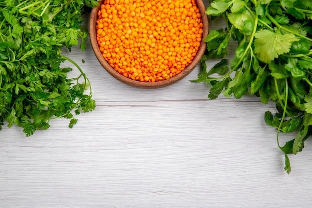 Vista superior do pacote de lentilha amarela de cogumelos verdes na mesa branca