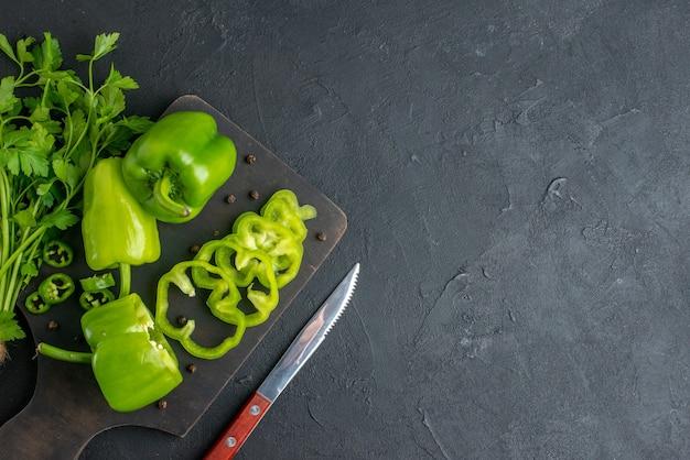 Vista superior do pacote verde de pimentas verdes frescas na faca de madeira da tábua de corte no lado direito na superfície preta angustiada