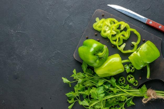 Vista superior do pacote verde de pimentas verdes frescas na faca de madeira da tábua de corte no lado esquerdo na superfície preta aflita