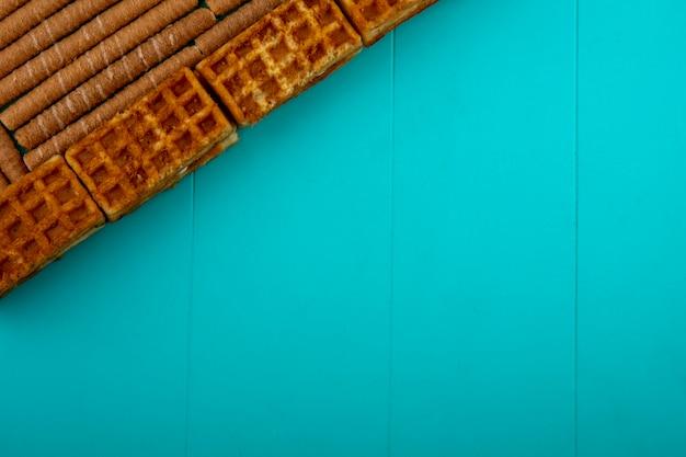 Vista superior do padrão de biscoitos e palitos crocantes sobre fundo azul, com espaço de cópia
