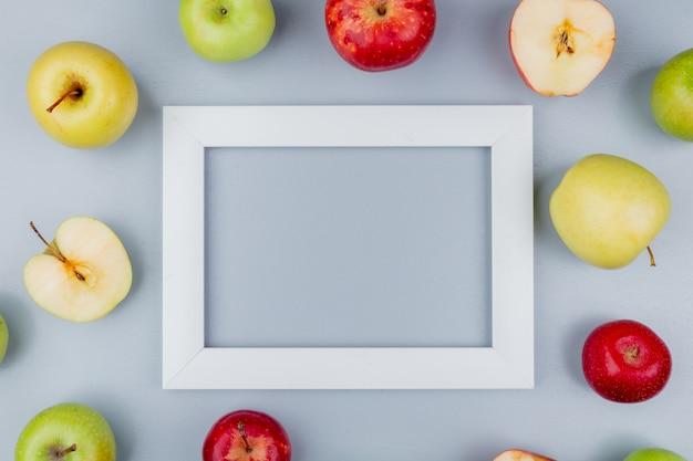 Vista superior do padrão de corte e maçãs inteiras em torno do quadro em fundo cinza com espaço de cópia