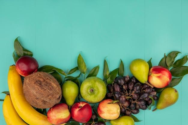 Vista superior do padrão de frutas como coco pera, pêssego, uva, maçã, banana, com folhas em fundo azul com espaço de cópia