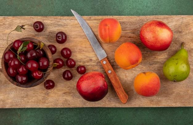 Vista superior do padrão de frutas como damascos, pêssegos, peras, cerejas com tigela de cereja e faca na tábua de corte sobre fundo verde