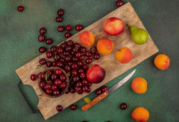 Vista superior do padrão de frutas como damascos, pêssegos, peras, cerejas com tigela de cereja na tábua de cortar com uma faca sobre fundo verde
