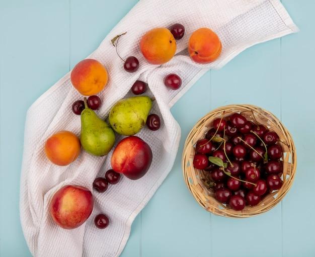 Vista superior do padrão de frutas como pêssego, damasco, pêra, cereja, num pano branco e uma cesta de cerejas no fundo azul