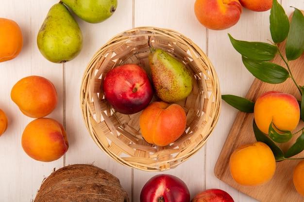 Vista superior do padrão de frutas como pêssego, pêra, damasco, na cesta e, pêssegos, na tábua, com, peras e, coco, em, madeira, fundo