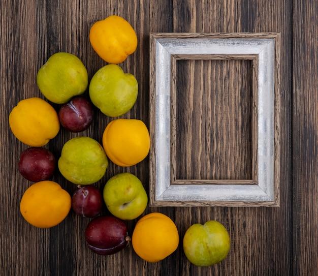 Vista superior do padrão de frutas como pluots e nectacots com moldura em fundo de madeira com espaço de cópia