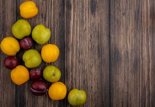 Vista superior do padrão de frutas, enquanto plumas verdes dão sabor a pluots reais e nectaculos em fundo de madeira com espaço de cópia