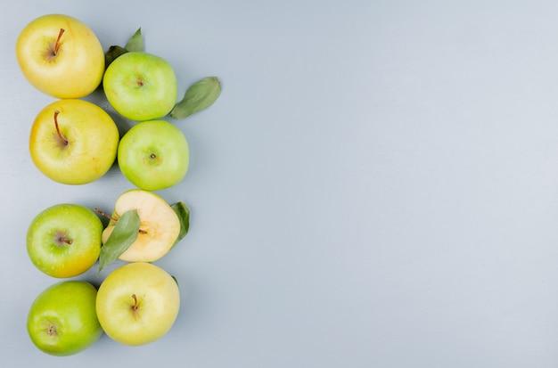 Vista superior do padrão de maçãs cortadas e inteiras no lado esquerdo e fundo cinza com espaço de cópia