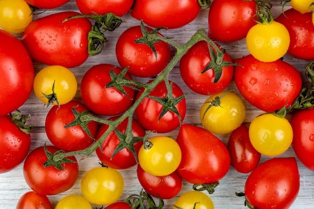 Vista superior do padrão de tomates amarelos e vermelhos na madeira
