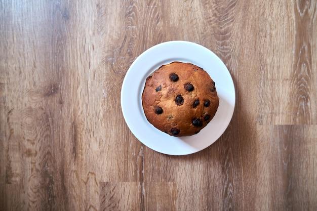 Vista superior do panetone de bolo de chocolate de natal em fundo de madeira com espaço de cópia em foco seletivo.