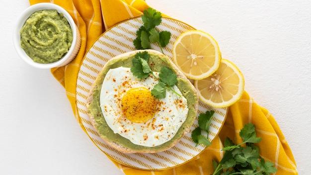 Vista superior do pão árabe com pasta de abacate e ovo frito no prato