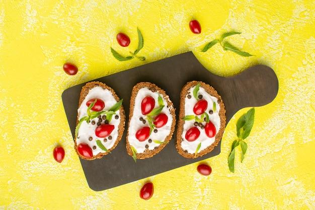 Vista superior do pão com creme junto com dogwood na superfície amarela