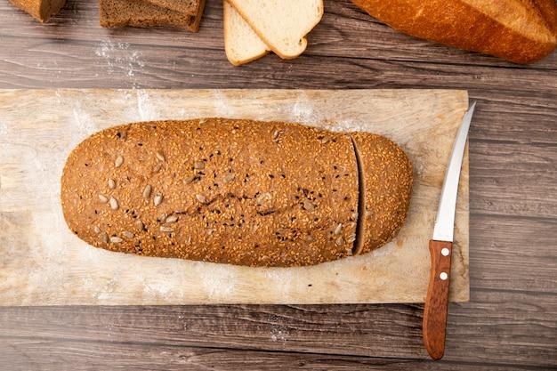 Vista superior do pão de forma cortada e faca na tábua no fundo de madeira