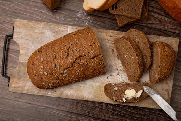 Vista superior do pão de forma cortado e fatiado, pão e fatia de pão com manteiga e faca na tábua sobre fundo de madeira
