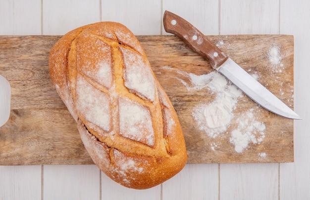 Vista superior do pão duro com faca e farinha na tábua de corte no fundo de madeira