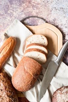 Vista superior do pão fatiado com toalha de cozinha e faca