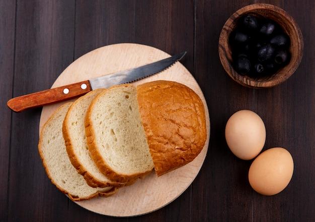 Vista superior do pão fatiado e faca na tábua com ovos e tigela de azeitona preta na superfície de madeira