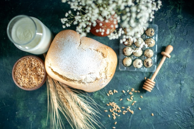 Vista superior do pão fresco com leite e ovos na superfície azul escura