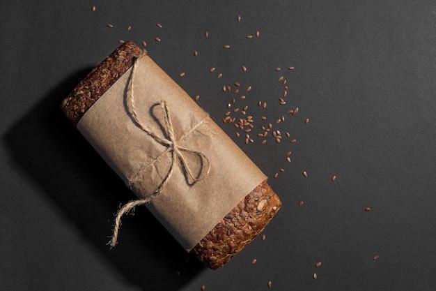 Vista superior do pão integral fatiado em fundo escuro, copie o espaço