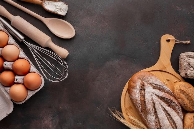 Vista superior do pão na placa de madeira com caixa de ovos